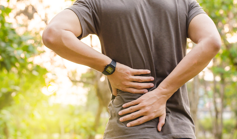 man has lower back pain in San Diego, CA