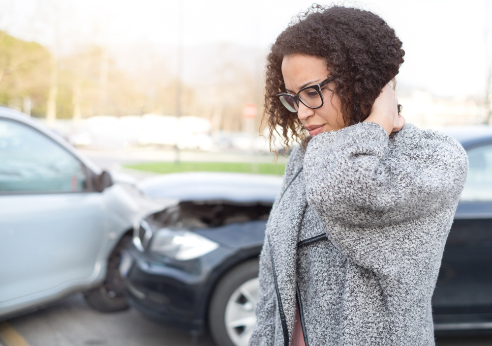 woman holding her neck in pain with an auto accident in the background