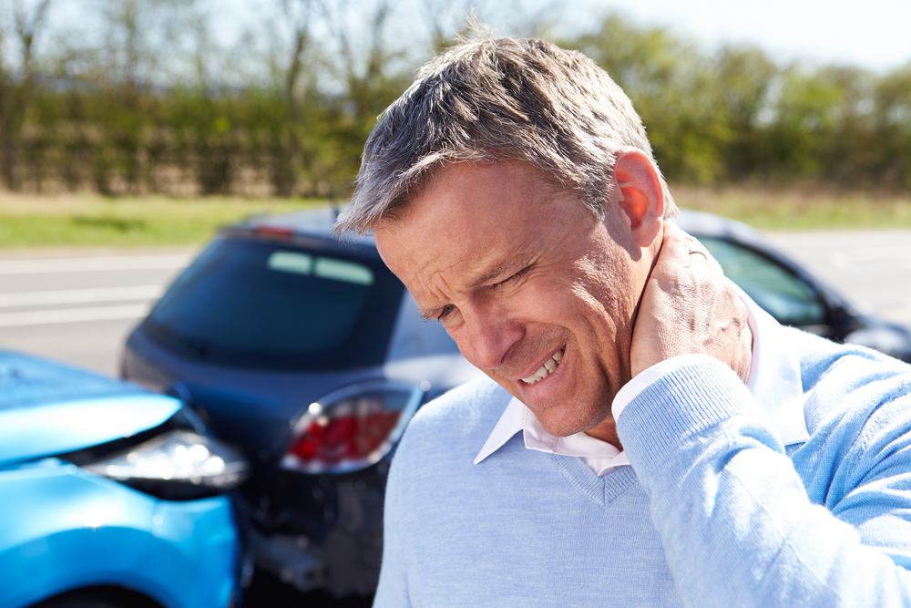 man holding neck from whiplash pain from an auto injury accident